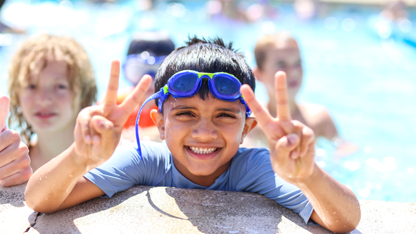 Boy camper giving peace signs in the pool