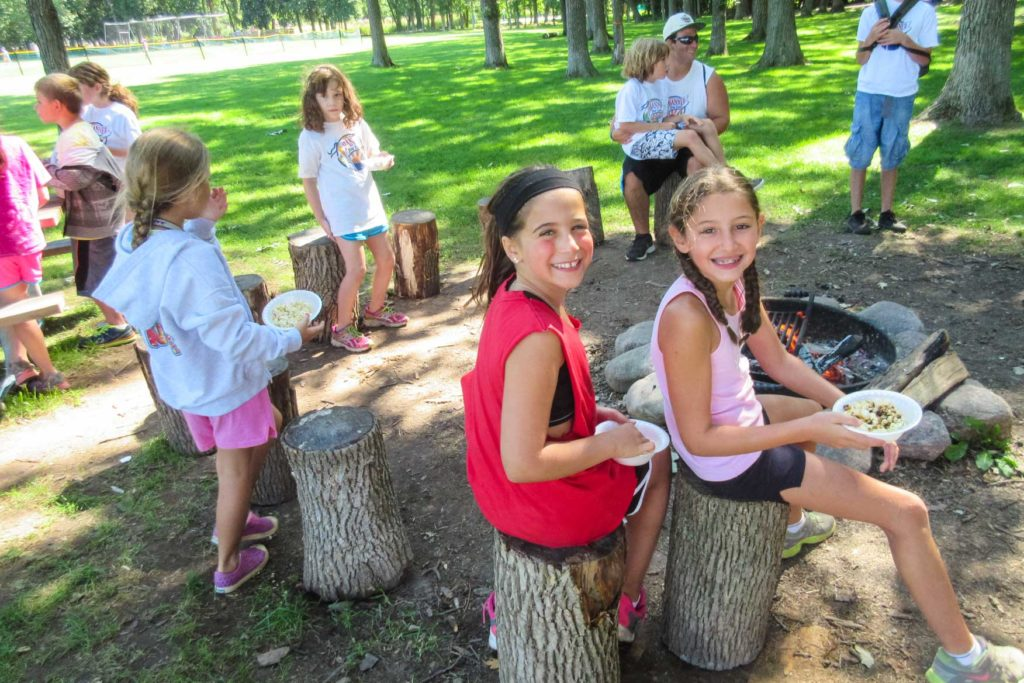 campers on tree stumps eating snacks