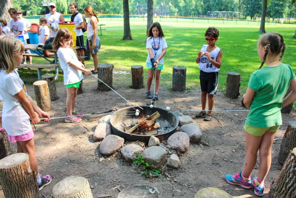 young children around a campfire roasting marshmallows