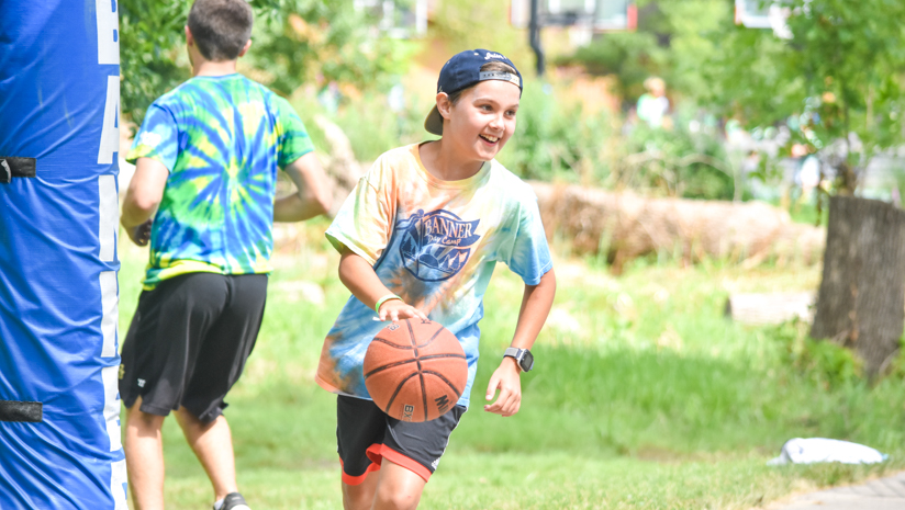 Boy camper playing basketball