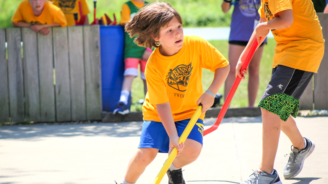 Camper running in a street hockey game