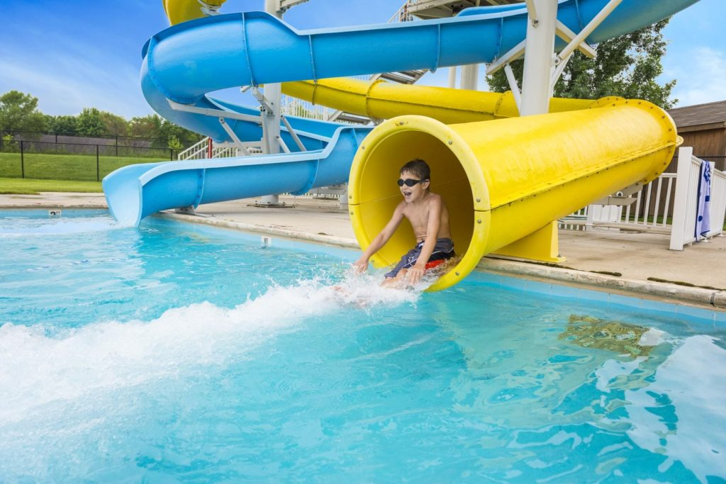 a boy exiting a water slide in the pool
