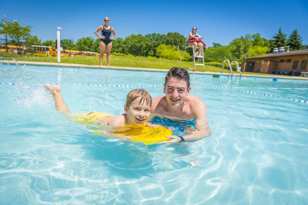 a counselor teaching a camper how to swim