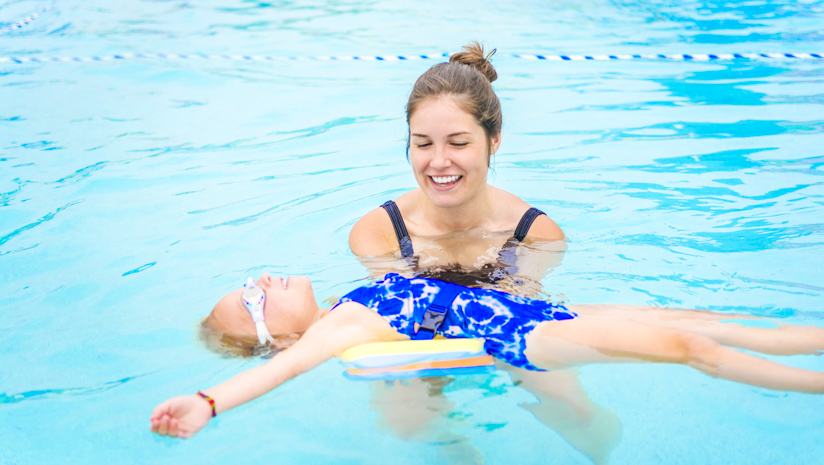 Female staff member teaching a girl camper how to swim in the pool