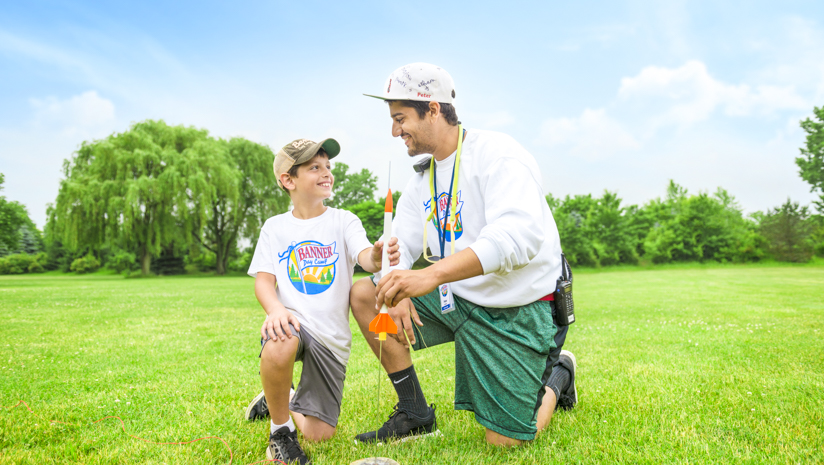 Male staff member helping a boy camper launch a rocket