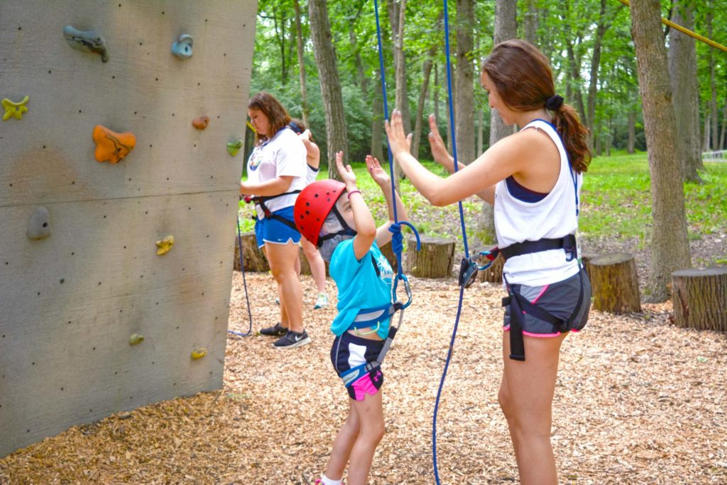A camper high fiving a counselor after conquering the rock wall