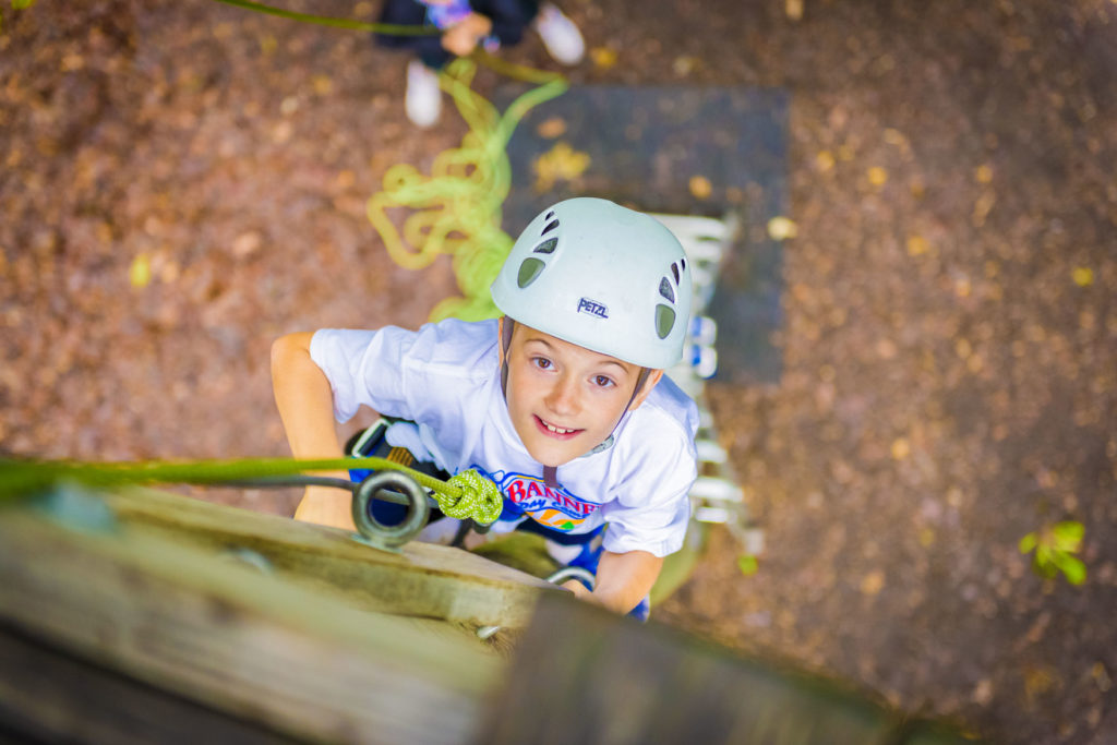 A boy looking up while climbing the rock wall