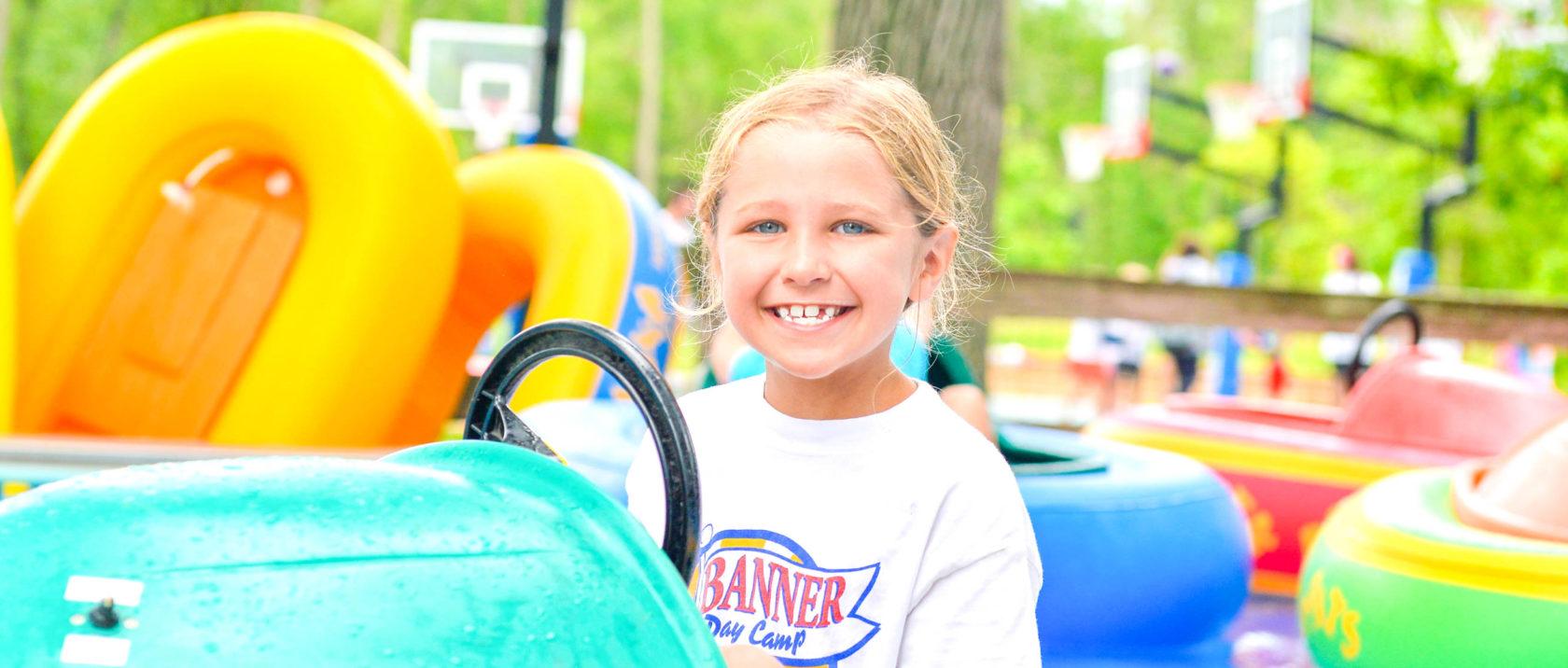 Girl camper smiling on a bumper boat