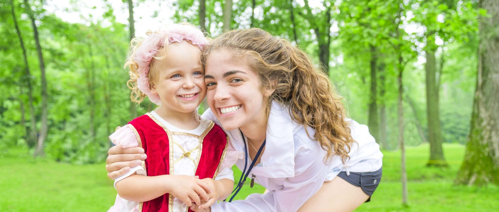 Female staff member smiling next to a young girl camper
