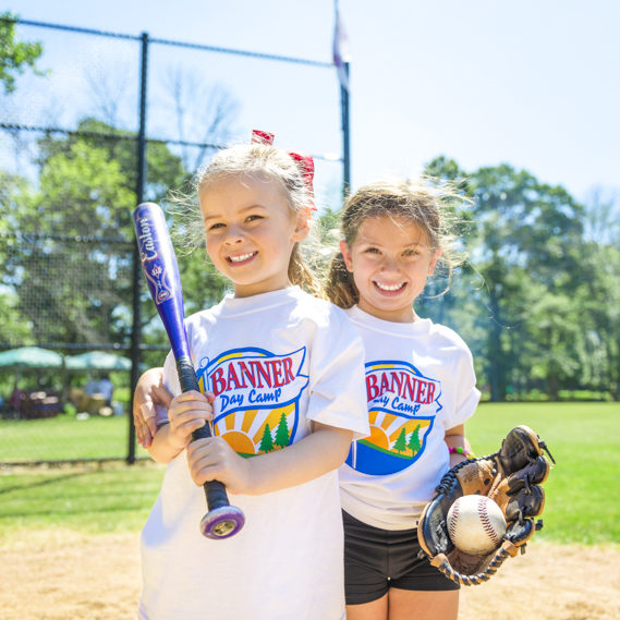 Two girl campers holding a softball bat and a softball glove