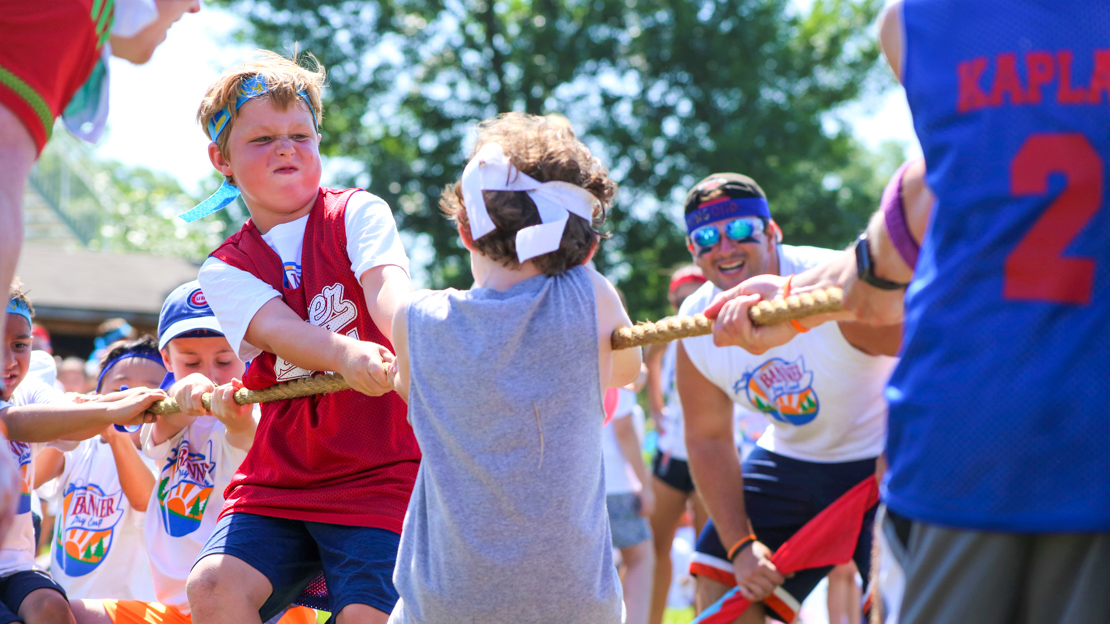Two boy campers playing tug-o-war