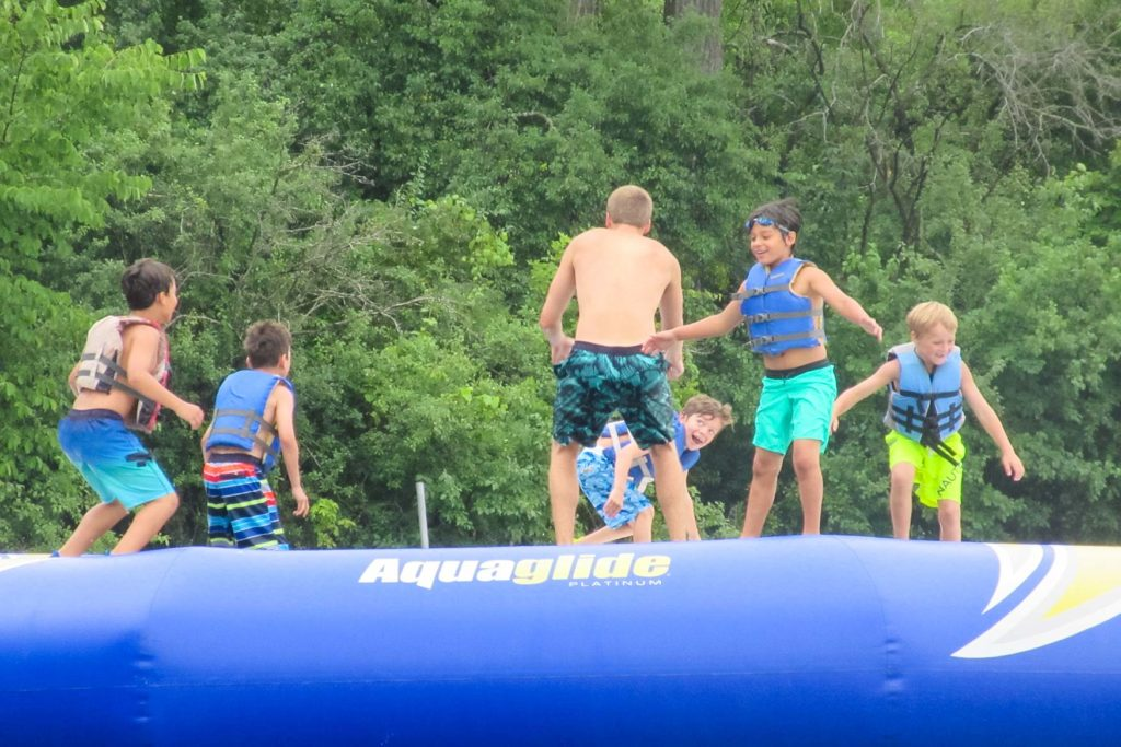Campers jumping on an inflatable trampoline
