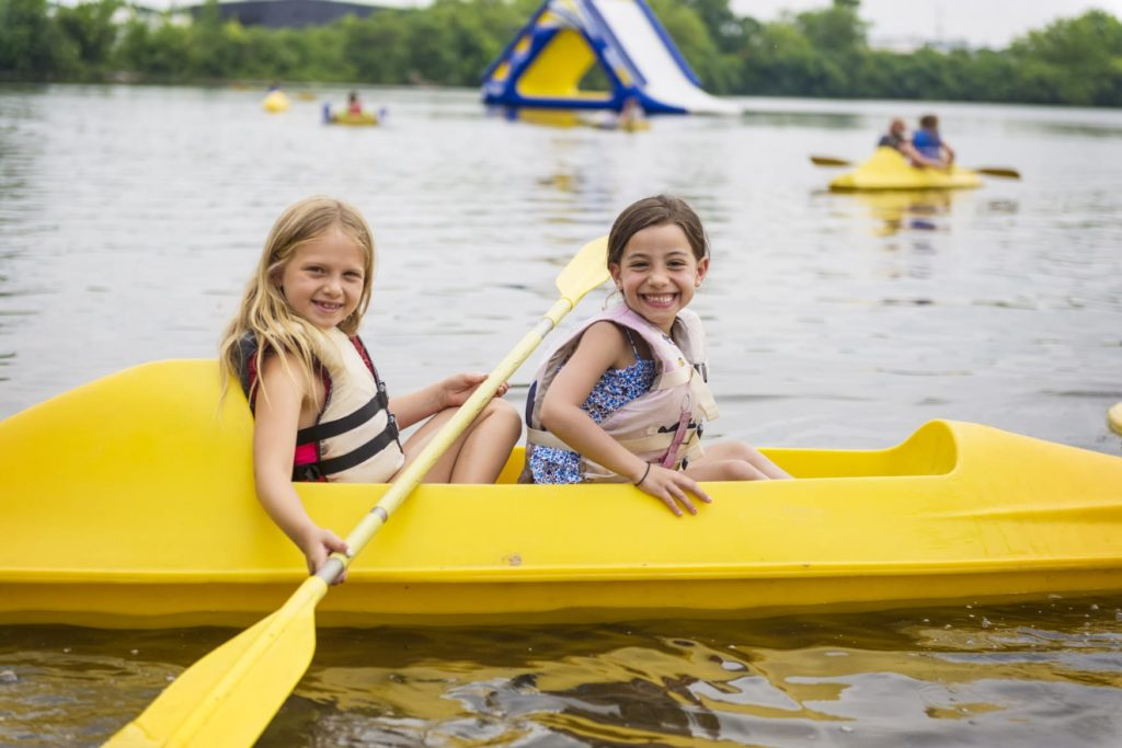 Two female campers in a yellow canoe on the lake