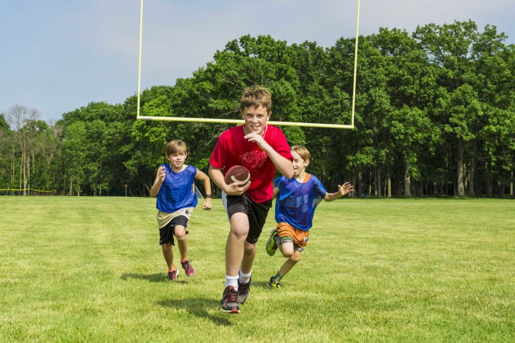 a boy running with a football with two boys behind him running