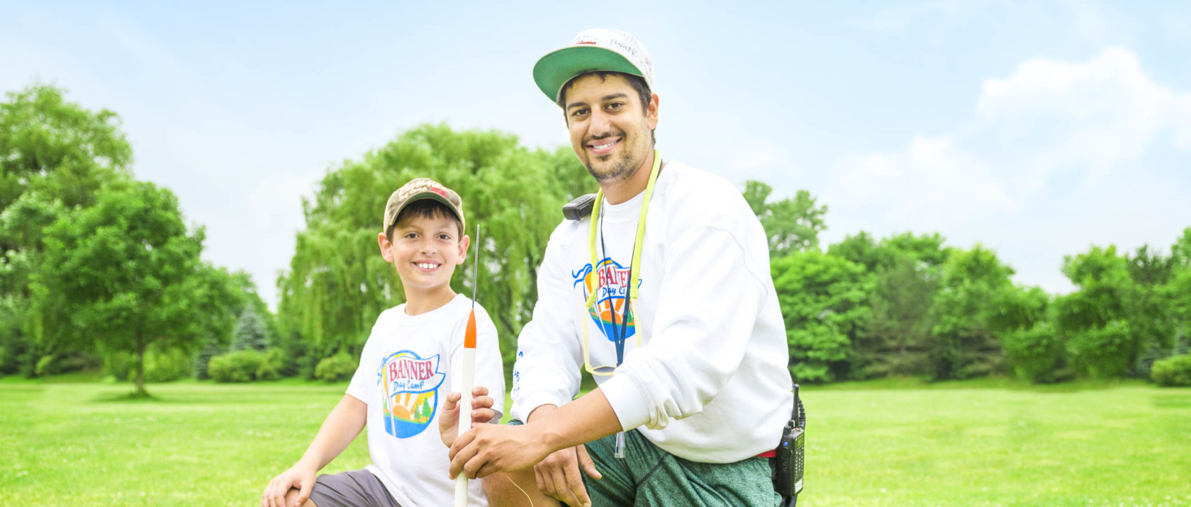 Male staff member helping a boy camper with a rocket launch