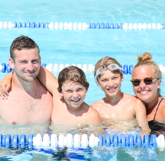 Two boy campers smiling in the pool with two staff members