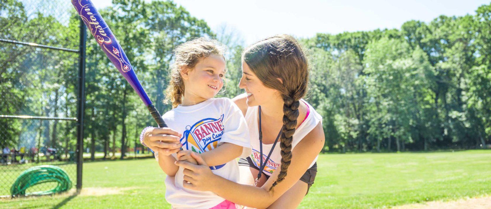 Staff member teaching a girl camper how to swing a softball bat