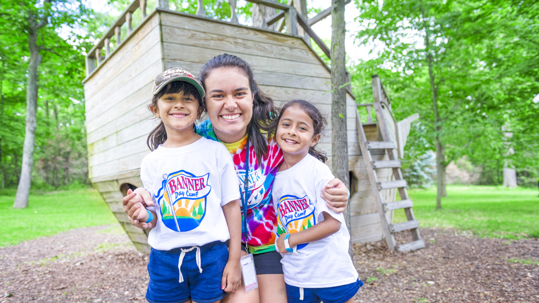 Female staff member smiling with two girl campers