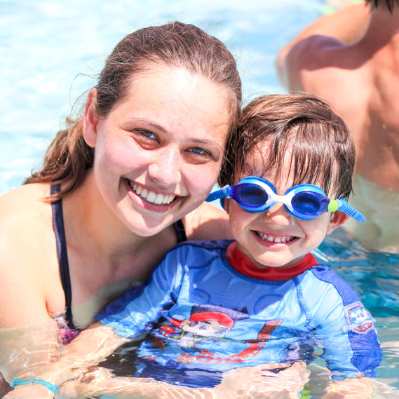 Boy camper with goggles in the pool with a staff member