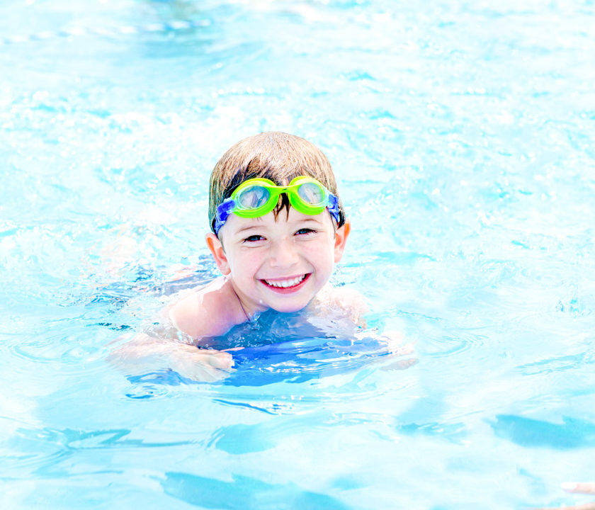 Boy camper smiling as he swims in the pool