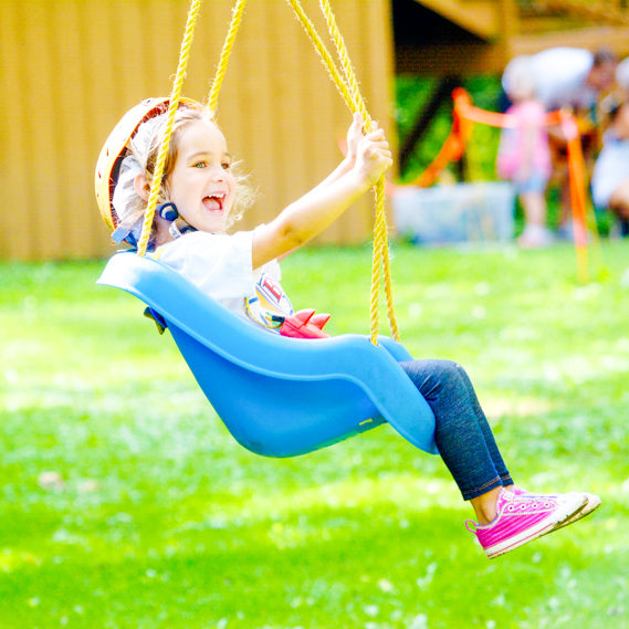 Girl camper smiling as she swings in a swing