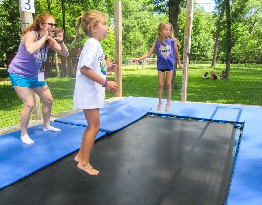 Two kids on the tramp court with a counselor behind them
