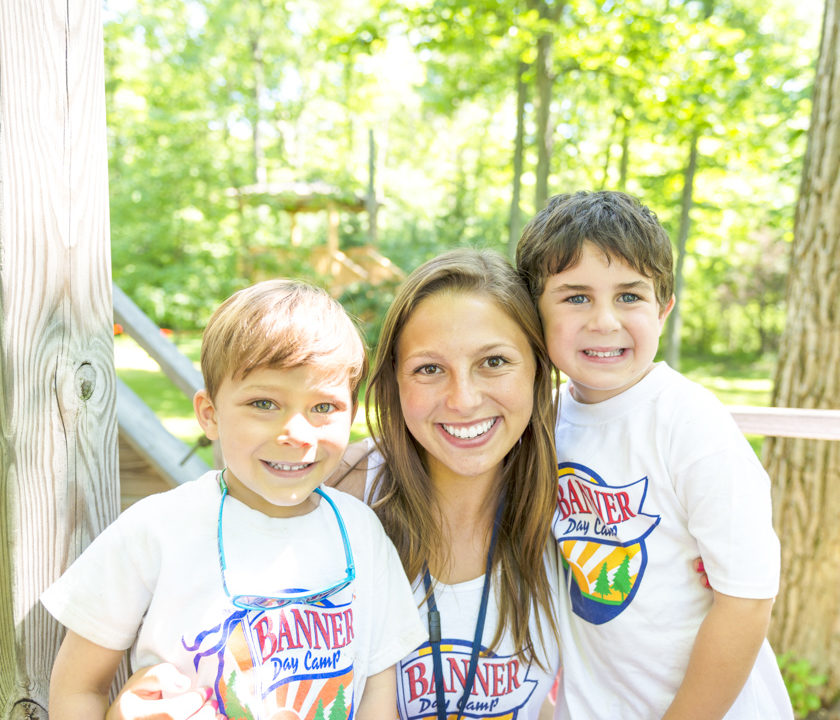 Two boy campers smiling with a female staff member