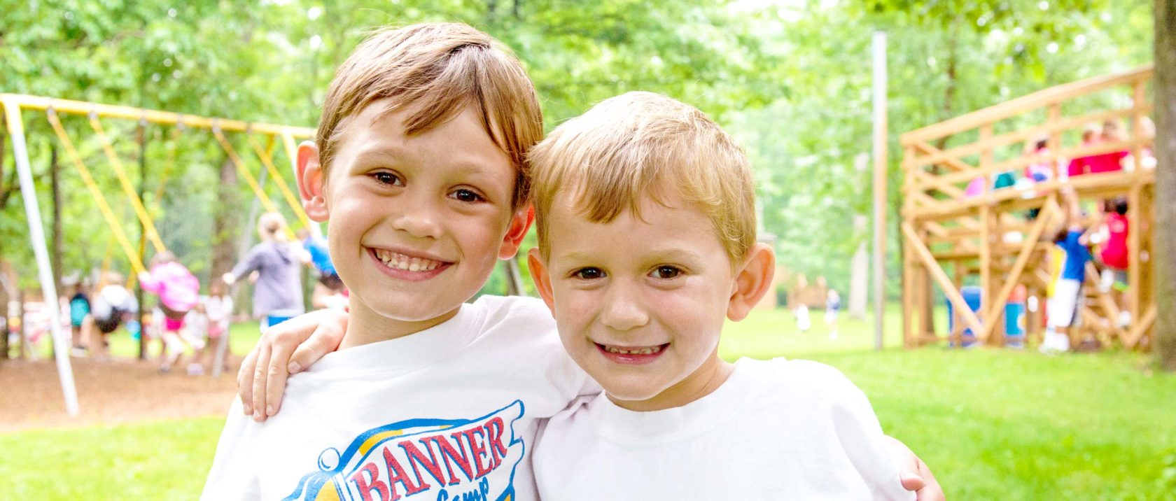 Two boy campers with arms around each other smiling