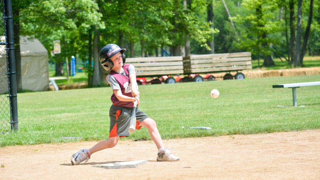 Camper swinging a bat at a baseball