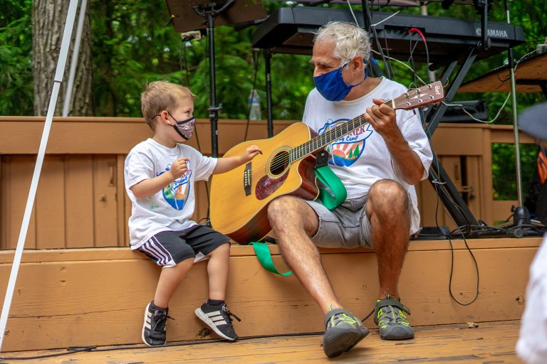 Young boy and older man playing the guitar together
