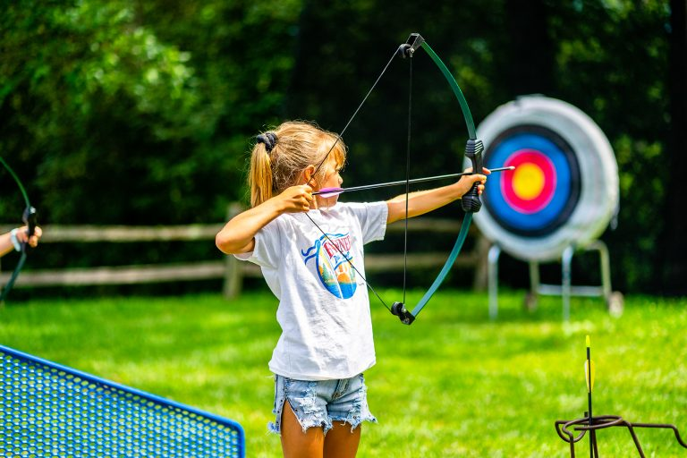 Young girl getting ready to shoot an arrow at a target on the archery field