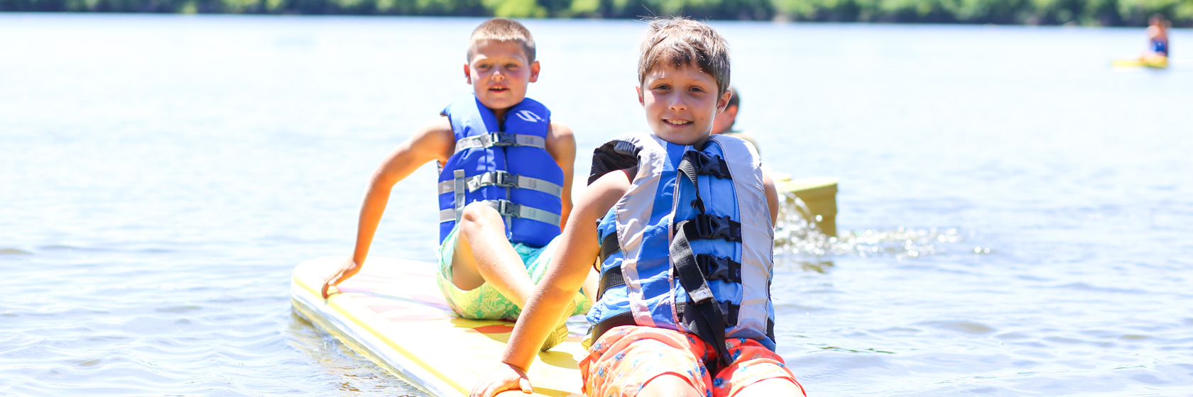 Two boy campers sitting on a paddle board in the lake