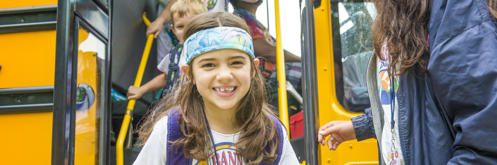 Camper smiling as she gets off the bus