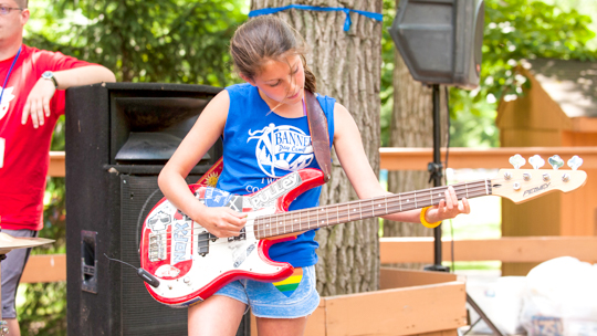 Girl camper playing the electric guitar on stage