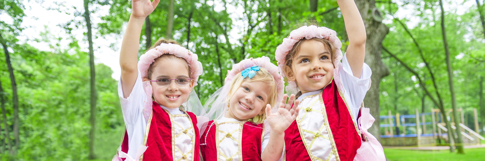 Three young girl campers all dressed up in the same princess dress smiling together