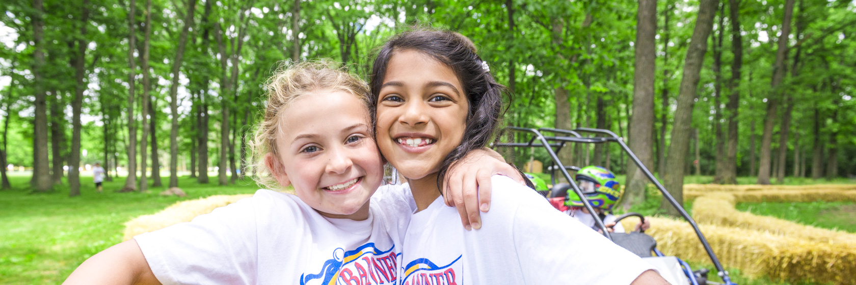 Two girl campers smiling with arms around each other on the go-kart course