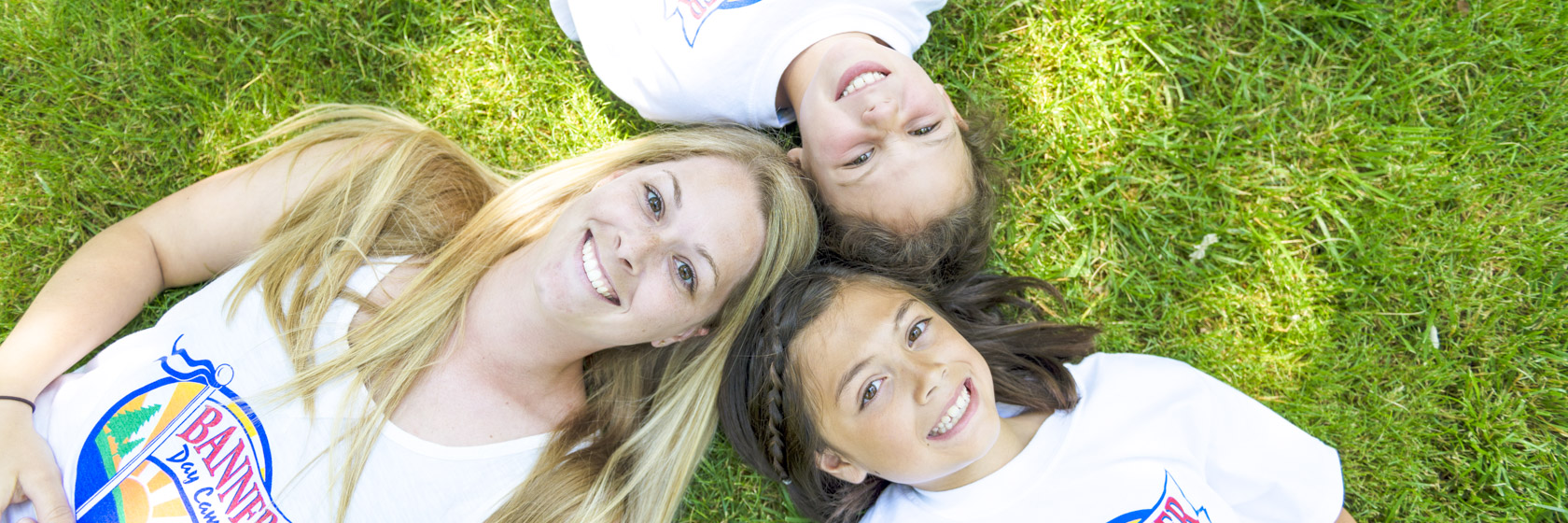Female counselor and two girl campers laying on the grass together with they heads together in a circle