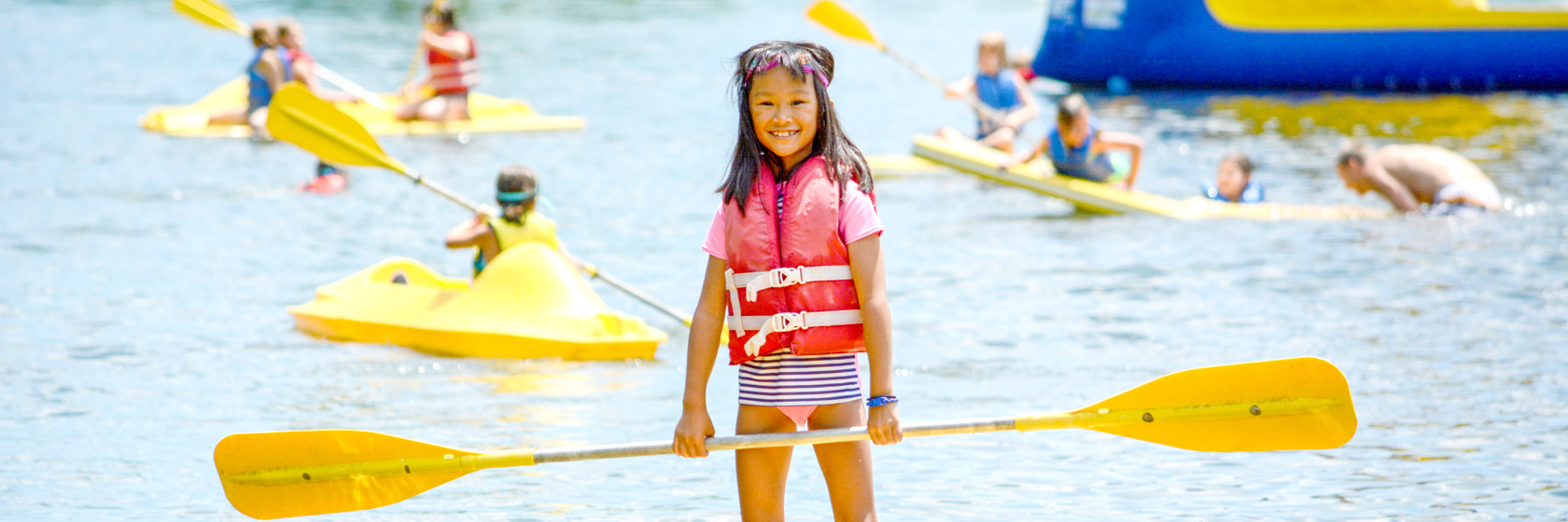 Girl camper standing up on a paddleboard in the lake smiling