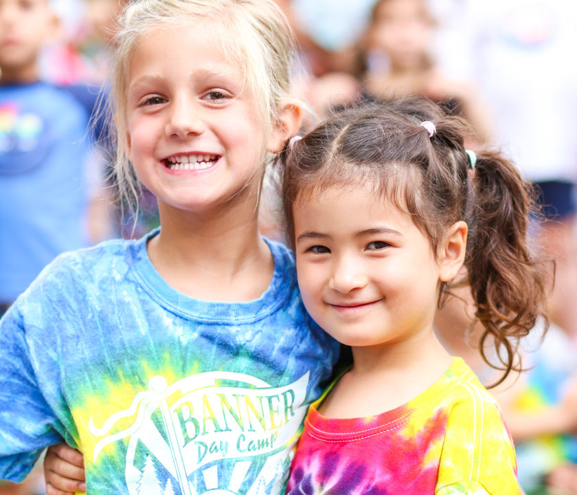 Two young campers in Banner shirts smiling together