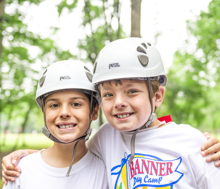 Two boy campers in helmets at the ziplining station smiling together