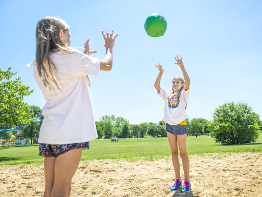 Two girl campers playing volleyball on the sand