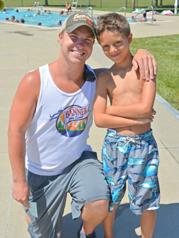 Male counselor with a male camper smiling by the pool