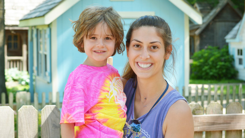Female counselor with girl camper smiling together