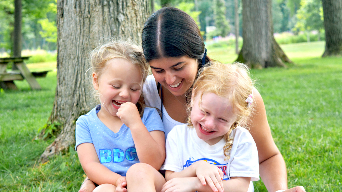 Female counselor with two young girl campers sitting on lap smiling