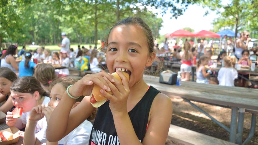 Girl camper eating a hot dog