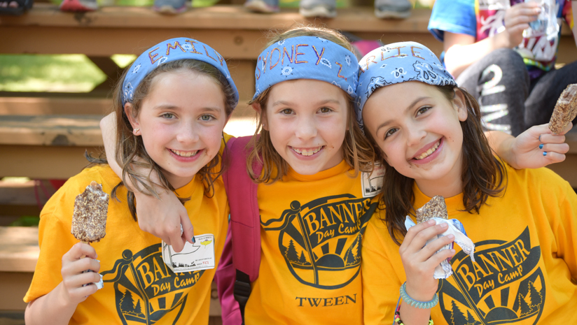Three girl campers smiling together with ice cream