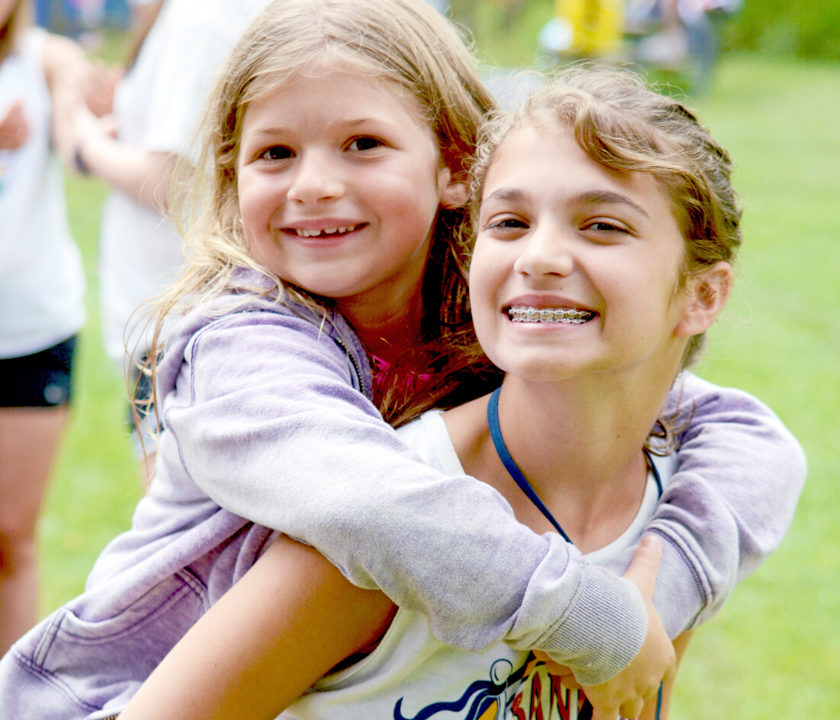 Female CIT camper giving a young girl a piggy back ride