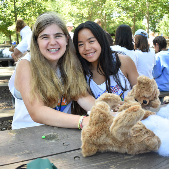 Two girl campers stuffing a stuffed animal