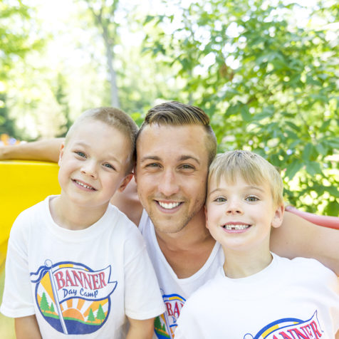 Male counselor smiling with two campers