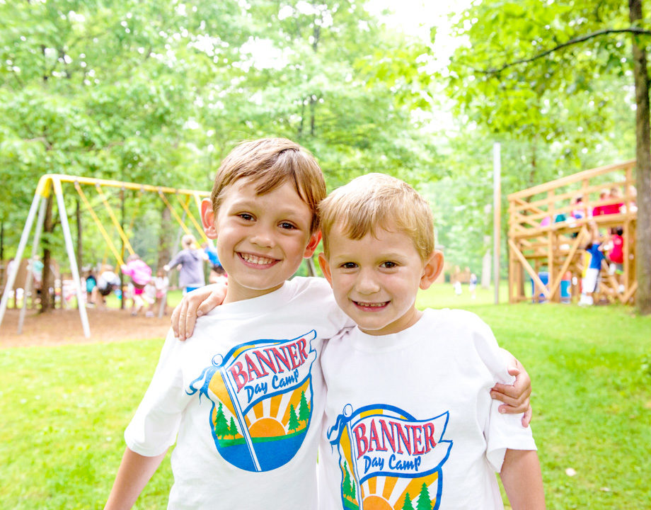 Two boy campers smiling together in Banner Day Camp shirts